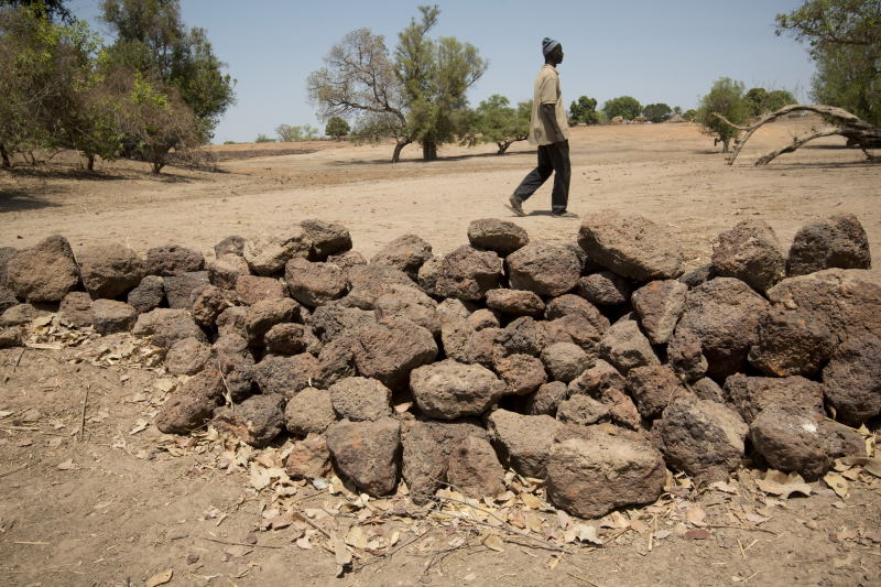 A stone barrier in a low-lying area will help impede erosion in a heavy rain event. Photo by Brett Eloff/Oxfam America.