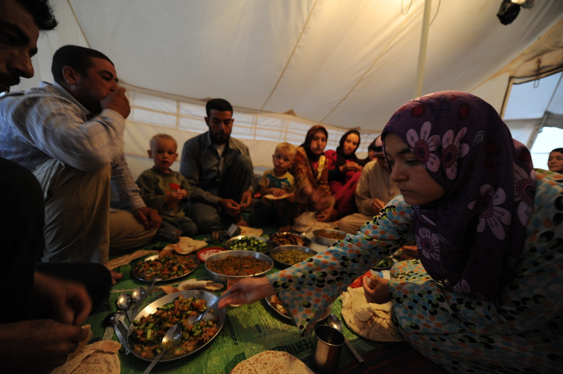 Um Ashraf's extended family unites to break their fast inside their tent on a farm in Jordan. Photo by: Karl Schembri/Oxfam