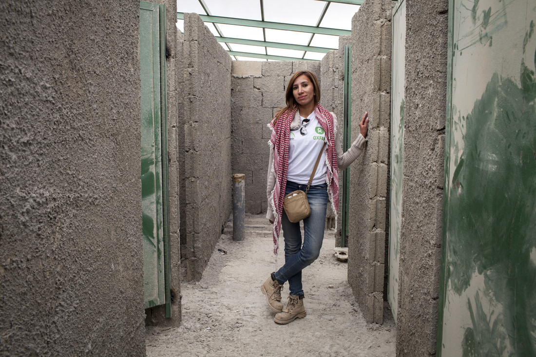 Oxfam engineer Farah Al-Basha stands in a partially constructed shower block that is currently being built at Zaatari Refugee Camp, Jordan. Photo: Anastasia Taylor-Lind/Oxfam