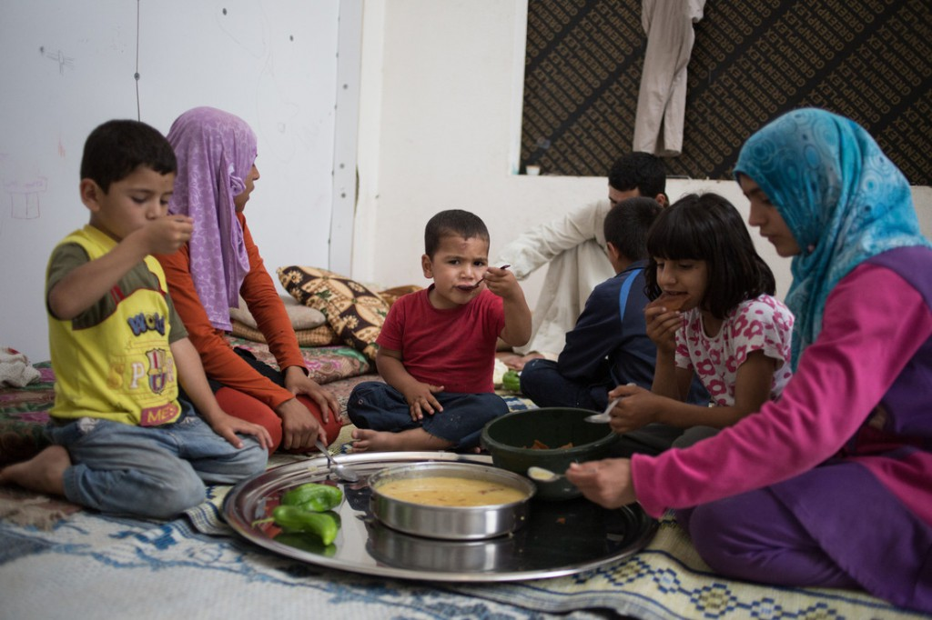 A refugee family living in the abandoned mall gathers together for a meal. Photo: Sam Tarling/Oxfam