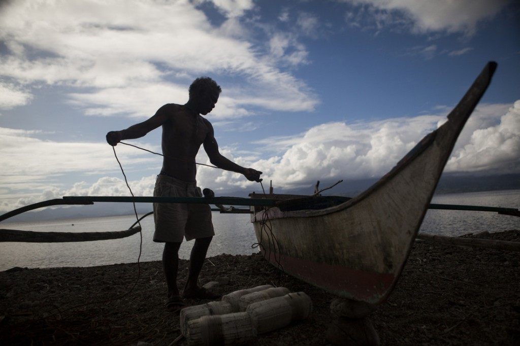 A fisherman in the Philippines with his boat in early 2013. Many people in coastal communities rely on fishing to earn a living. Photo: Simon Rawles/Oxfam