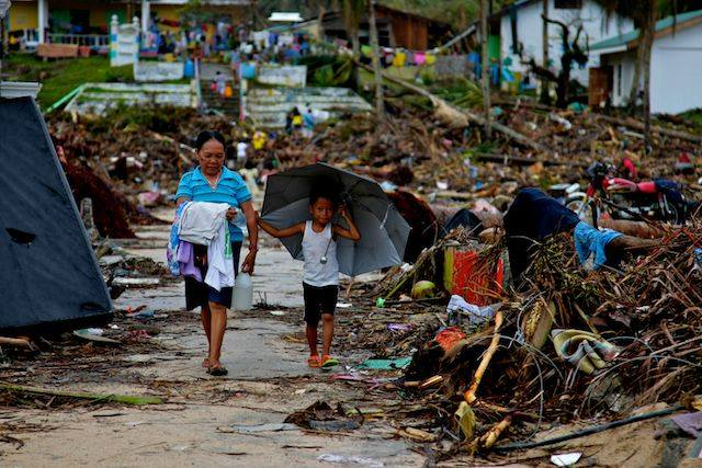 Residents in Samar walk past the wreckage left by one of the most powerful storms in recorded history. Photo: Jire Carreon / Oxfam