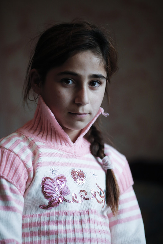 Froua Yousef, 9, wears new clothes that her mother, Enaam, has just bought for her with a $40 voucher supplied by Oxfam, with the assistance of partner agency JAK, in Qalamoun, north Lebanon. Photo: Sam Tarling/Oxfam