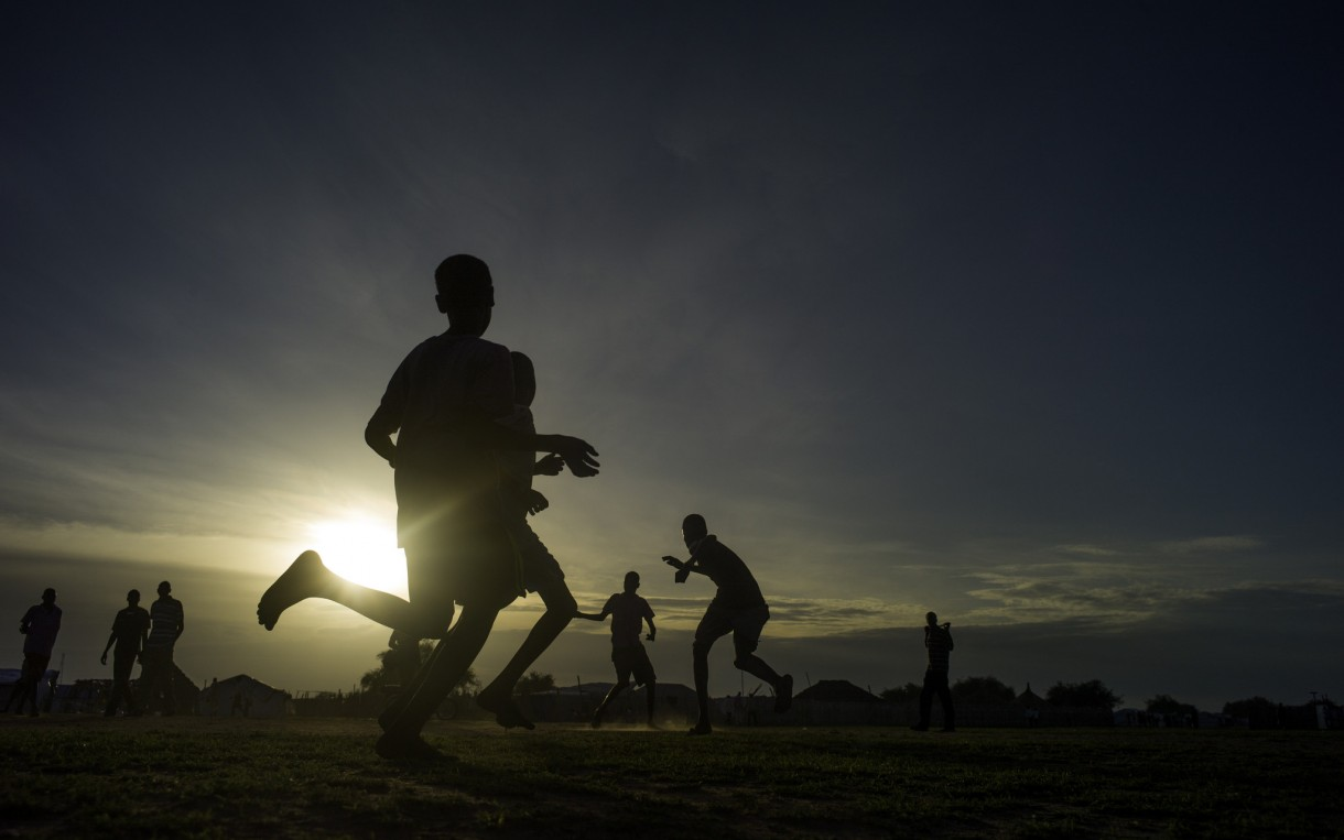 Children play soccer as the sun sets over a  camp for displaced people in Mingkaman, South Sudan. Oxfam is working in the camp to provide clean water and sanitation. Photo: Kieran Doherty/Oxfam