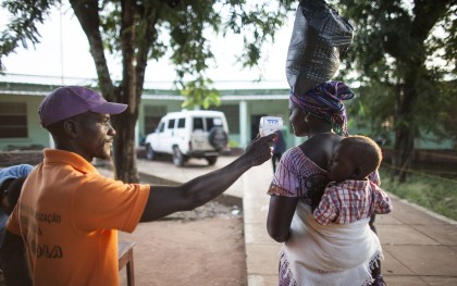 A NADEL outreach worker at an Ebola checkpoint takes the temperature of each person entering the Tombali regional hospital. Though there have been no cases of Ebola in Guinea-Bissau, Tombali is considered very vulnerable. Photo: Jane Hahn / Oxfam America