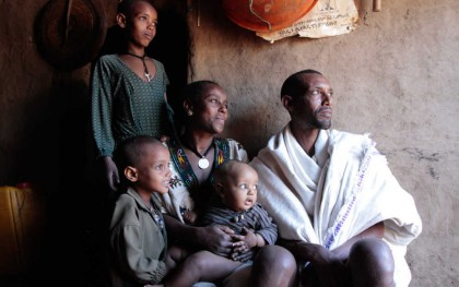 Getie Adugna, his wife Bosena Mekete, and their children sit in the doorway of their home in the village of Michael Debir. Photo by Coco McCabe/Oxfam America