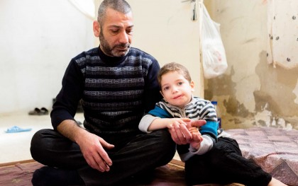 Abed with one of his sons in their small Amman flat. The Syrian refugee works illegally to pay rent, while he awaits resettlement to the US. He lost the youngest of his five children who suffered from a heart condition and passed away in Jordan where he couldn't get the required medical help. Photo: Thomas Louapre