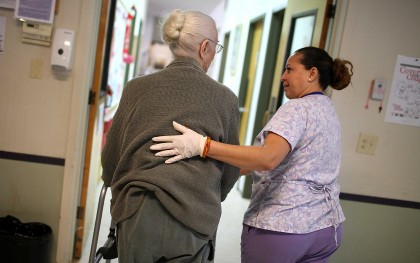 Mayra Dittman (R) helps Juanita Gilbert walk to the restroom at an Adult Day Health Care Center in Novato, California. The mean hourly wage of personal care aides is slightly over $10; the occupation is nearly 90 percent female. Photo: Justin Sullivan/Getty Images