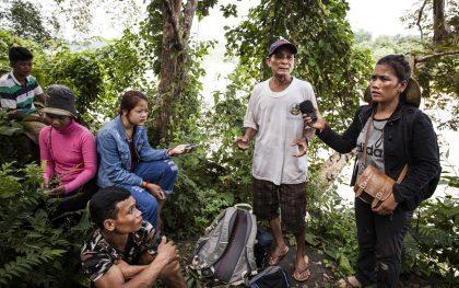 Ping Chamroeun (right) interviews Houn Kaleb at a sacred site above the Sesan River in northern Ratanakiri province, Cambodia. Photo by Patrick Brown/Panos for Oxfam America