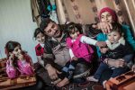 Abu Omar played with his five daughters in their caravan in Zaatari refugee camp in Jordan. Pablo Tosco / Oxfam