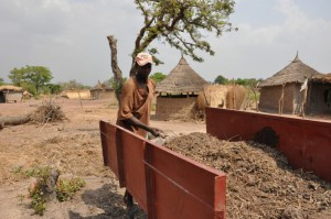 Issuf Sangare, 26, loads organic fertilizer into a cart he received from his growers' cooperative in Faragouran, Mali. The Robin Hood Tax would provide new funding for development programs worldwide.  Photo by Chris Hufstader/Oxfam America