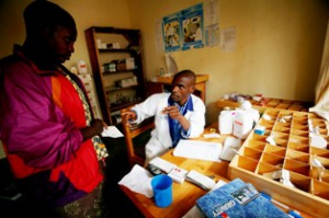 A nurse supplies a female patient with a prescription at Kibuga health center in Kibuga, Rwanda. Photo by Kate Hold/Oxfam