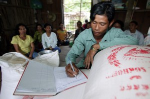 Dy Yong keeps the books for the rice Bank Committee so that everybody can see how it run and maintained at the Rice cooperative in Takom village, Battambang. The rice store committee has many members and they introduce villagers to the principles of trading rice to give them security at a much reduced rate than the market offers. Photo by Jim Holmes/Oxfam.