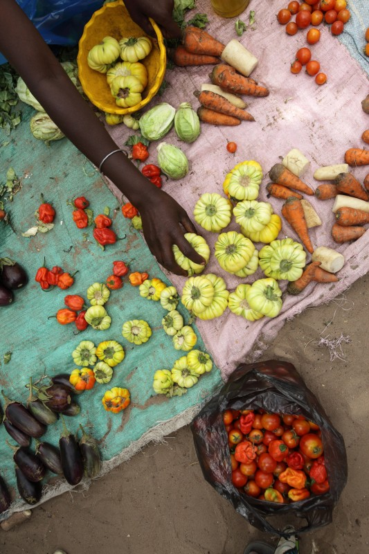 A vegetable seller measures bitter eggplants grown in Touba Ngembe for a customer in the village market of Ndiaganiao, Senegal. Photo: Rebecca Blackwell / Oxfam America