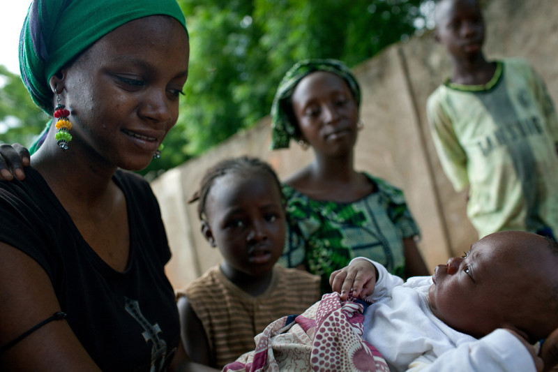 "Dienabou Diamanka, left, holds her baby brother Ibrahima Diaw, while Ibrahima's mom Rouby Ndiaye (in green) and other family members watch on in Tankanto Escale village, Senegal last year. Their family participated in the Oxfam/FODDE cash program. Her father, Alassane Diaw, said, ""Cash is better than food. With cash, I can choose to buy fish and rice; people receiving food don't have this possibility. [And] there is another reason the cash is useful: if one of my children is sick, I can use this money to go to the hospital. Without money, I cannot go."""
