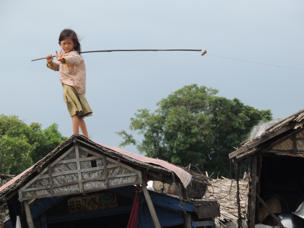 A child atop a house in the Tonlé Sap region of Cambodia waves while holding a fishing pole. Photo: Jeffrey Buchanan