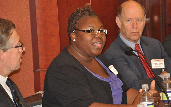 Tianna Gaines-Turner, center, speaks to a Capitol Hill forum on realities of life for the millions of working poor in the US. Listening is Andrew Yarrow of Oxfam America (left) and Eugene Steuerle of the Urban Institute (right). Photo: Oxfam America.