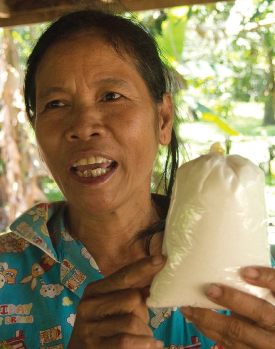 Yon Ny of Koh Kong province, Cambodia, holds a bag of sugar. She had 24 acres of land before it was taken and cleared to make way for sugar plantations. Photo: Caroline Gluck / Oxfam