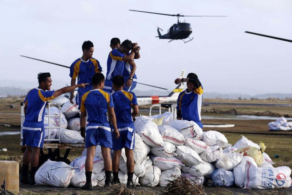 Filipino air force personnel prepare to load sacks of relief goods at the airport in the devastated city of Tacloban, in Leyte province. Current estimates are that the typhoon has affected 9.68 million people, or about two million families. Photo by EPA/Dennis M. Sabangan.