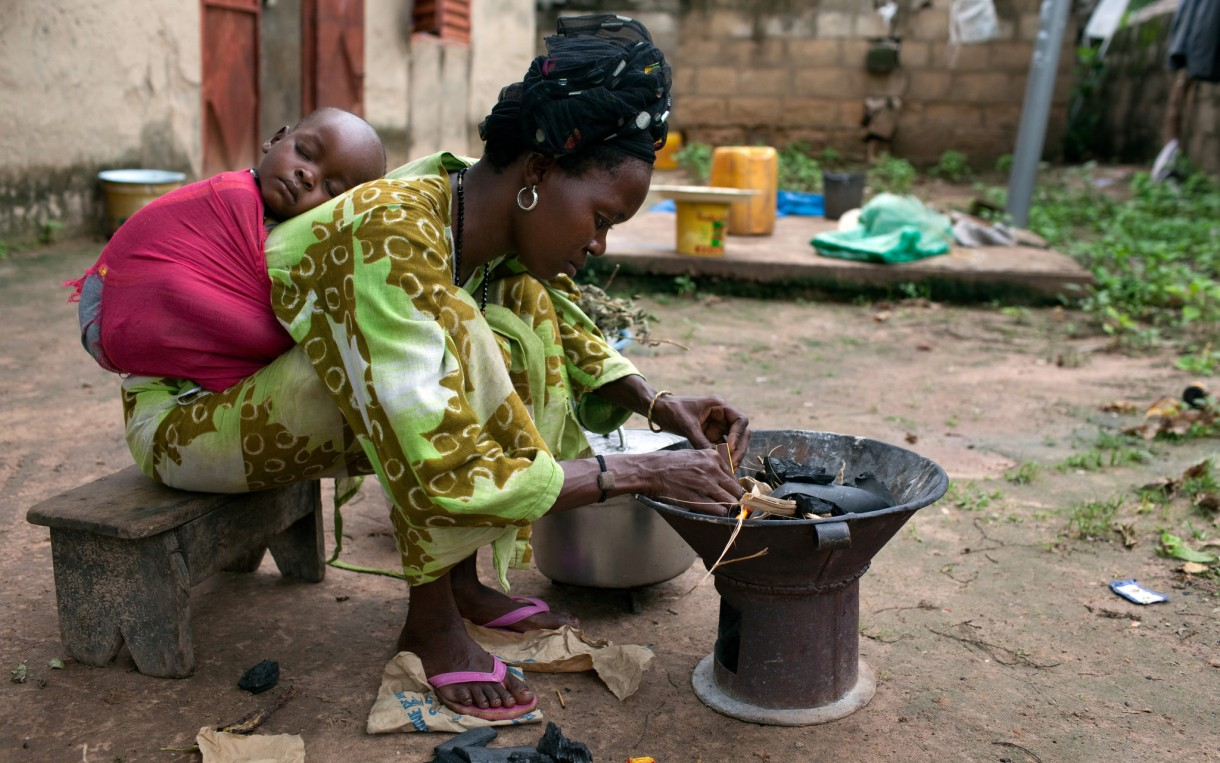 Food vendor Dado Sade builds a fire to begin cooking supper at her home in Kolda, Senegal.  Her 2-year-old child, Daude Mballo, sleeps nearby. Photo: Holly Pickett / Oxfam America