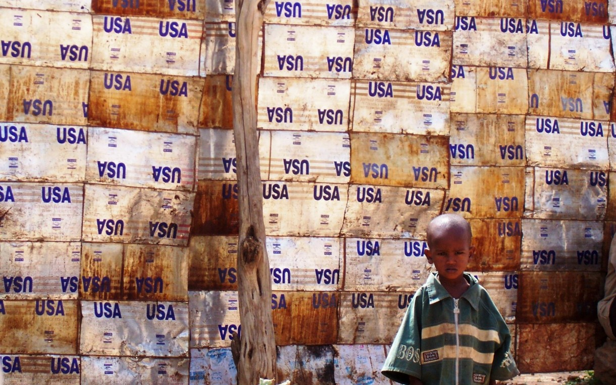 USA Wall, Dire Dawa, Ethiopia: Child leaning against wall made of USAID food aid containers in the flood-destroyed area of Bahere Tsege in Dire Dawa. Photo: Liz Lucas/Oxfam America