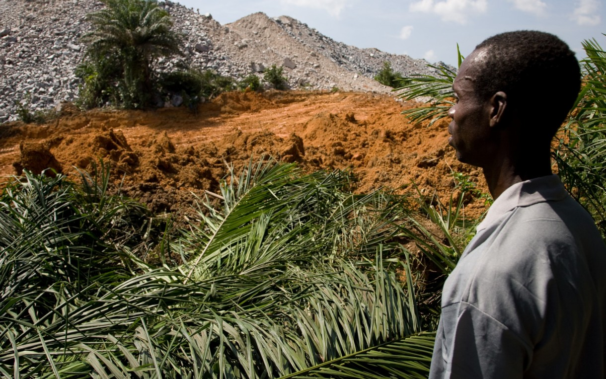 Waste rock from a nearby mine is encroaching on the relocated village of Teberebie, Ghana. Communities relocated to make way for gold mines in Ghana struggle with loss of agricultural land, unemployment, and environmental damage. Photo: Neil Brander/Oxfam America