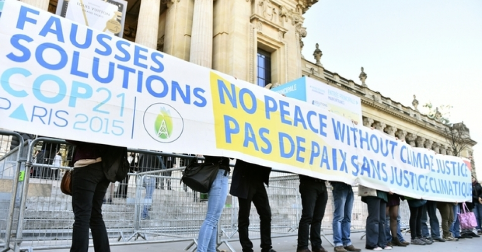 "Demonstrators with banner reading: ""false solutions COP21 No peace without climate justice"" in front of the ""Solutions COP21"" exhibition at the Grand Palais in Paris. Photo: AFP"