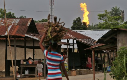 A girl walk along a street while Oshie gas flare belonging to Agip oil company burns in Akaraolu community Rivers State, Niger Delta area of Nigeria June 2015. (Photo: George Osodi / Panos for Oxfam America)
