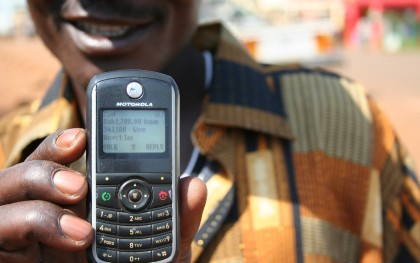 Man holds his cell phone displaying the electronic receipt of his cash transfer. Photo: Give Directly
