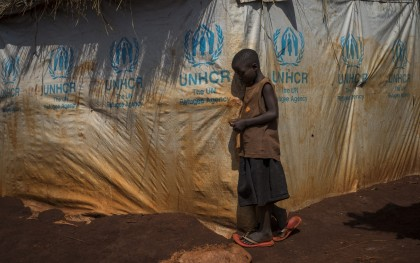 """A Burundian refugee child stands outside a makeshift shelter in the Nyarugusu refugee camp in Tanzania on March 26, 2016. According to UNHCR, Nyarugusu is """"one of the largest and most overcrowded refugee camps in the world,"""" currently hosting over 140,000 refugees but built to accommodate only 50,000. The camp has a resident population of around 60,000 Congolese refugees, with an influx of around 78,000 Burundian refugees since last year. (Photo: Phil Moore / Oxfam)"""
