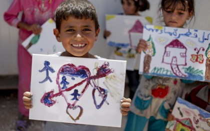 Khalil, 7, displays a tile he has painted for his family in Zataari Refugee Camp. (Photo: Sam Tarling / Oxfam America)