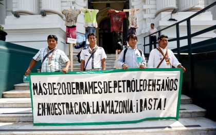 """Indigenous leaders present 8,000 signatures from 74 countries asking the Peruvian government to remediate environmental pollution. Their banner reads: """"More than 20 oil spills in 5 years in our home, the Amazon. Enough!"""" (Photo: Oxfam Peru)"""