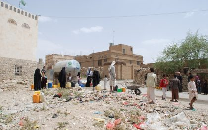 People gather around a water tank provided by Oxfam in Khamir, a district in Amran governorate hosting many IDPs. Oxfam engineers have repaired an existing water network here so 30% of families in the town can now have access running water for the first time in 7 years. Clean safe drinking water is still being trucked into the town for everyone, including the IDPs. Plans to connect the rest of the town to the main network are underway. (Photo: Kate Wiggans / Oxfam)