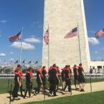 Members of the #OrangeVest performance group walk by the Washington Monument on the way to the DC Rally 4 Refugees. (Photo: Rebecca Gilbert / Oxfam America)