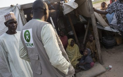 An Oxfam food security officer talks to a family at a camp for displaced people in the Kushari neighborhood of Maiduguri, the capital of Borno state in Nigeria. Photo by Sam Tarling/Oxfam