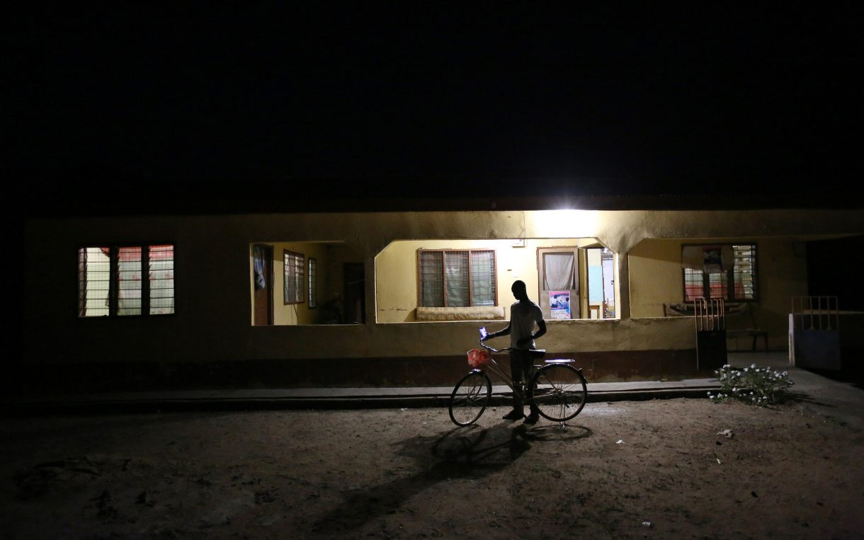 boy outside health clinic with electricity access electrification