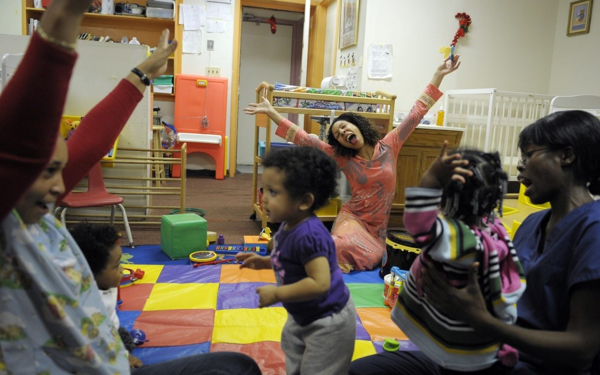 children and staff working women play at a child care center