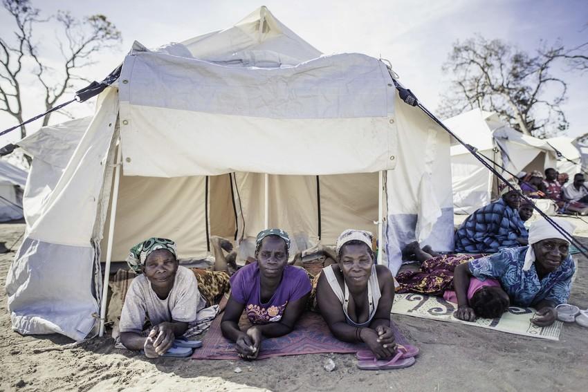 cyclone survivors sit under a tent in mozambique