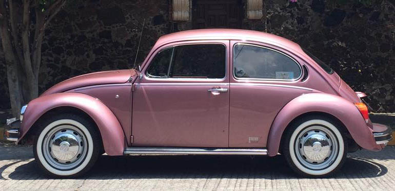 Volkswagen Sedán Edition One color rosa estacionado frente a una casa.