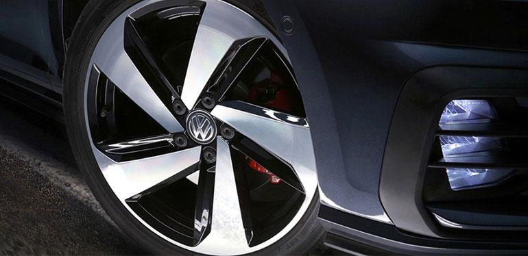 Acercamiento al rin de un auto Volkswagen color negro con sus faros encendidos