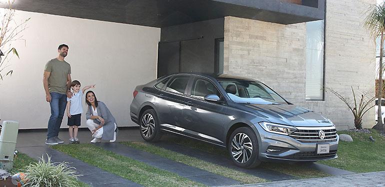 Familia reunida en una casa junto con el Nuevo Jetta 2019 de Volkswagen