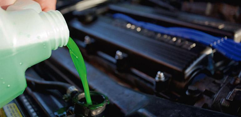 Líquido refrigernate siendo vaciado en el radiador de un auto Volkswagen