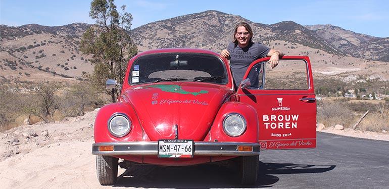 Dirk posando junto a su Vocho de Volkswagen en una carretera del desierto mexicano