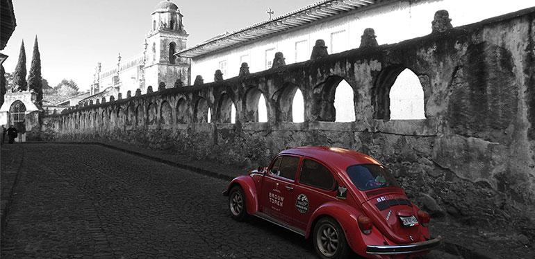 Rocinante, el Vocho rojo de Dirk, recorriendo calles enmarcadas por arcos de piedra