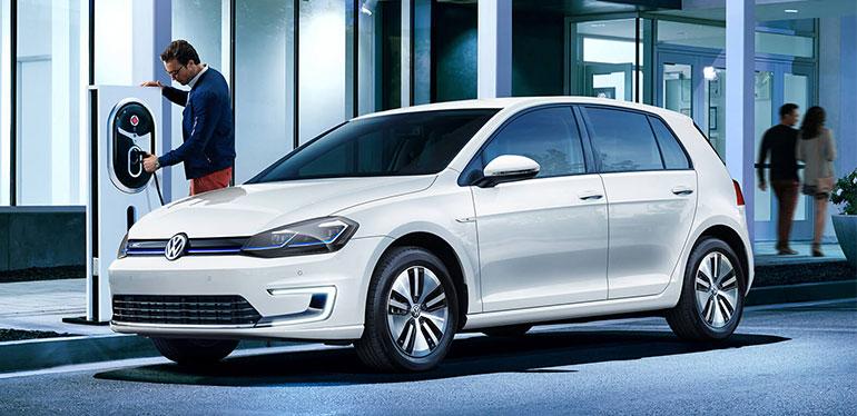 Hombre cargando su e-Golf auto eléctrico de Volkswagen
