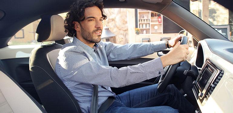 Hombre manejando un Beetle obtenido con Volkswagen Financial Services