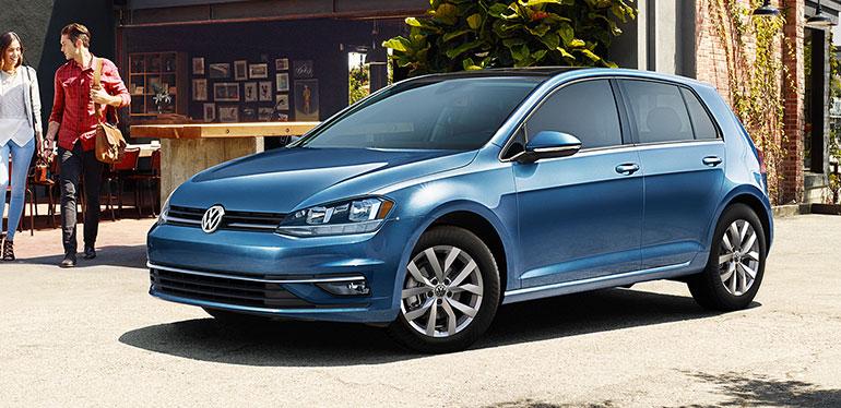 Pareja caminando hacia su auto Golf obtenido con Volkswagen Financial Services