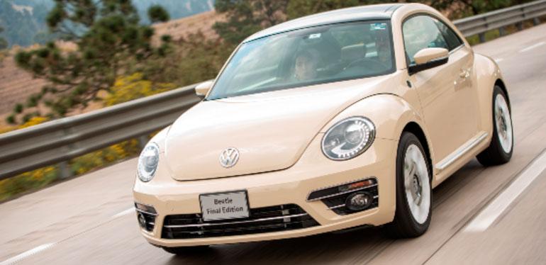 Beetle de Volkswagen Final Edition en color Reedbeige andando en una autopista con árboles detrás