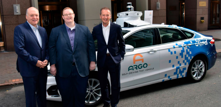 Diess Hacket y Salesky parados frente auto blanco con logo de Argo AI