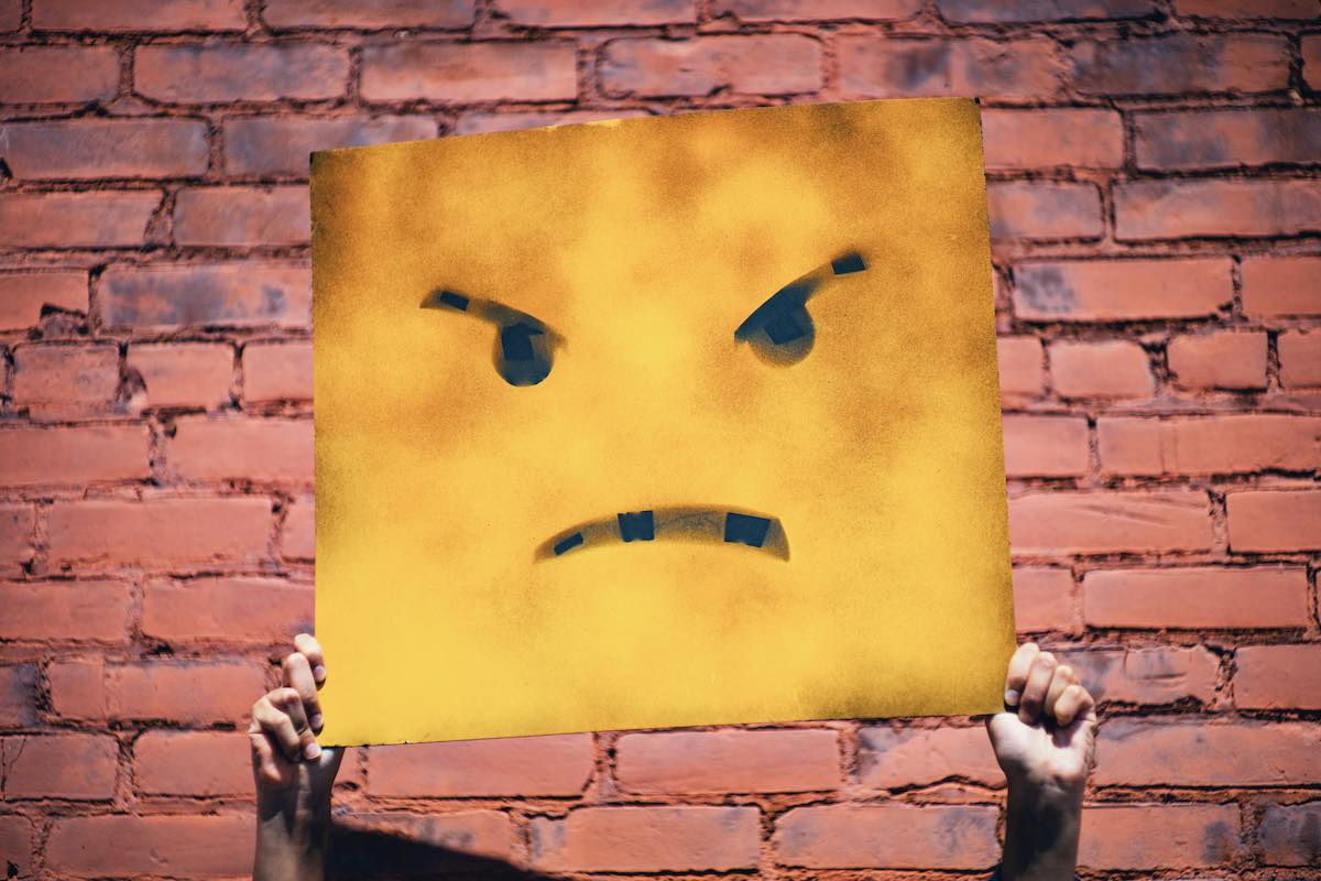 Person holding angry poster infront of brick wall